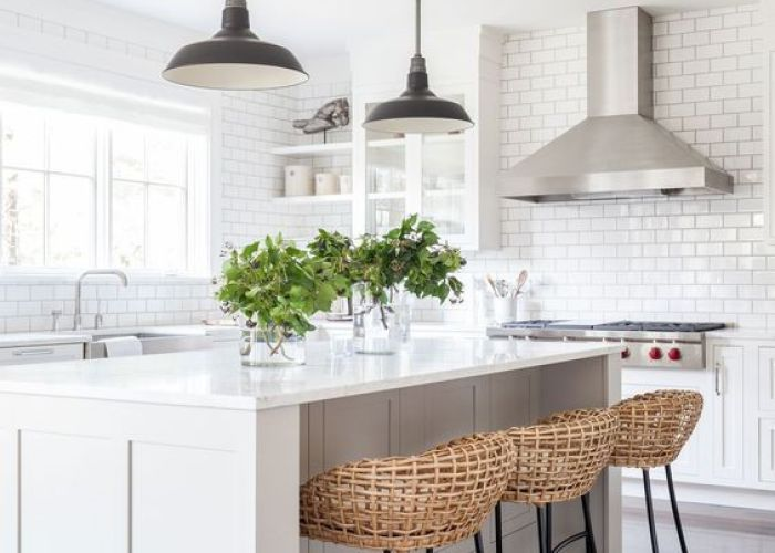 White kitchen featuring subway tiles open shelving glass front cabinets light hardwood flooring  large island with seating and vintage indust  also