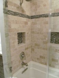 The shower surround is a travertine tile. The accent tile ...