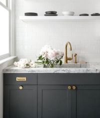 Dark gray kitchen cabinets accented with aged brass knobs ...