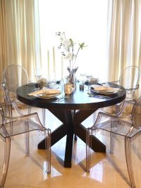 This elegant dining room features a large round wood ...