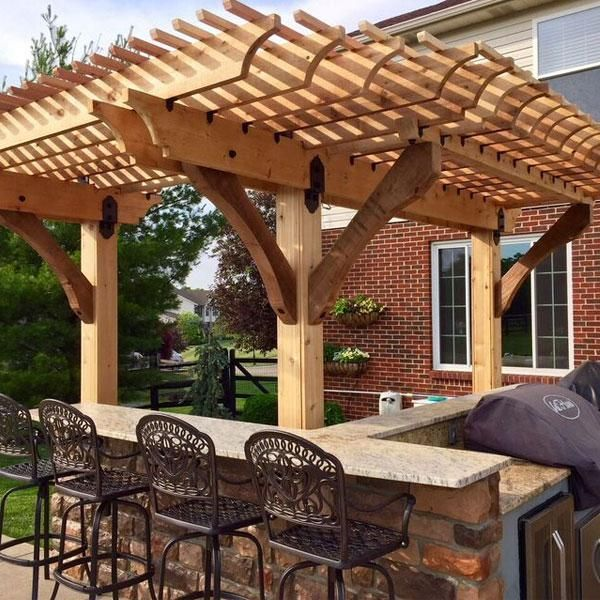 This image features a pergola, built over a patio grill