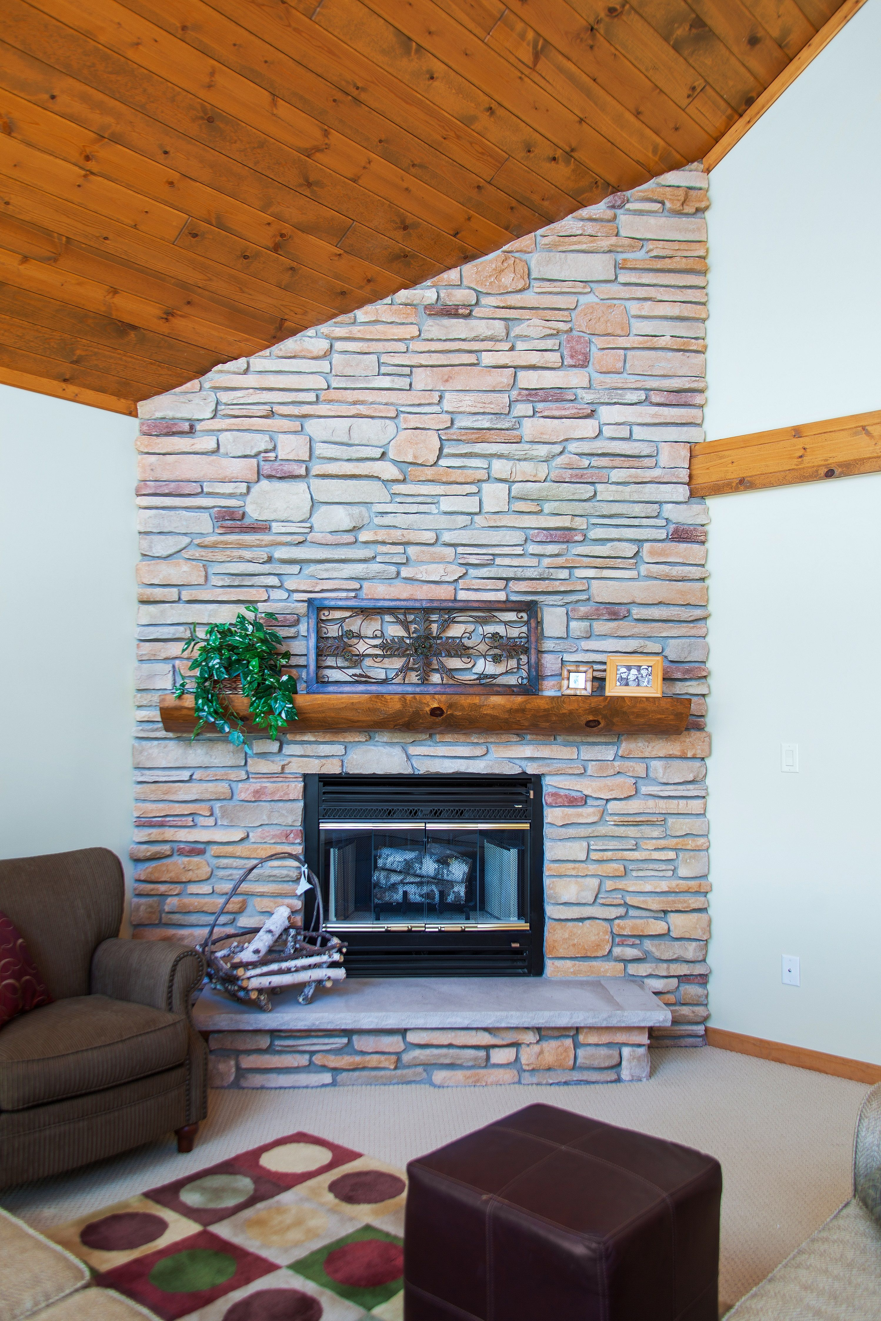 Limestone fireplace with a split log mantle and stone hearth Wood covered cathedral ceiling and