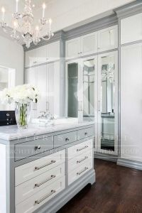 White and gray closet features a gray cabinets fitted with ...
