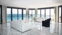 Living room with a white polished marble floor and with a ...
