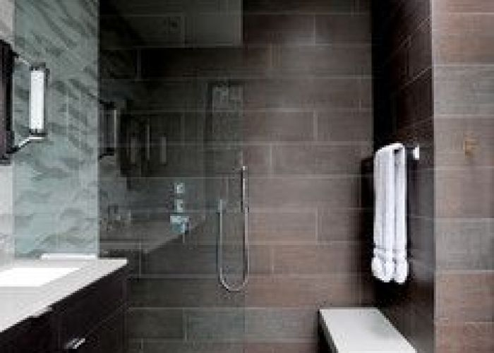 Contemporary bathroom with curbless shower floor floating bench vanity mounted to  tiled wall and also