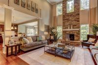 Windows flank a soaring stone fireplace in this two-story ...