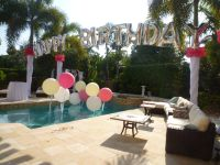 Birthday balloon arch over a swimming pool. Backyard party ...