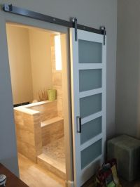This satin-etched glass contemporary barn door with ...