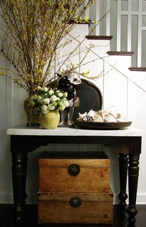 entry way table with room for shoes underneath and keys on top in a basket perha
