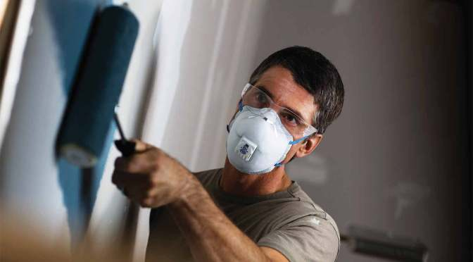 contractor using a disposable particulate respirator with carbon embedded in the filter media
