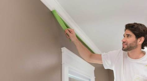 contractor removing FrogTape from crown moulding