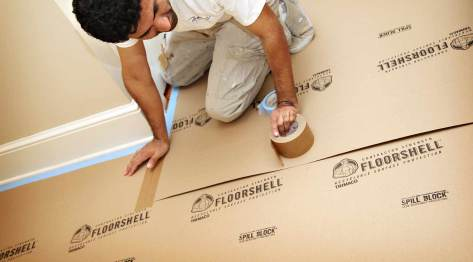 a contractor installing FloorShell® Heavy Duty Temporary Surface Protector