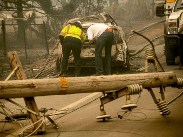FILE - In this Nov. 10, 2018 file photo, with a downed power utility pole in the foreground, Eric England, right, searches through a friends vehicle after the wildfire burned through Paradise, Calif. California's largest utility company is getting b