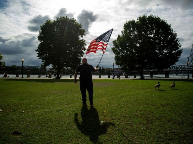 PHOTO: A member of the Proud Boys, who declined to give his name, carries a flag before the start of a protest in Portland, Ore., on Saturday, Aug. 17, 2019.