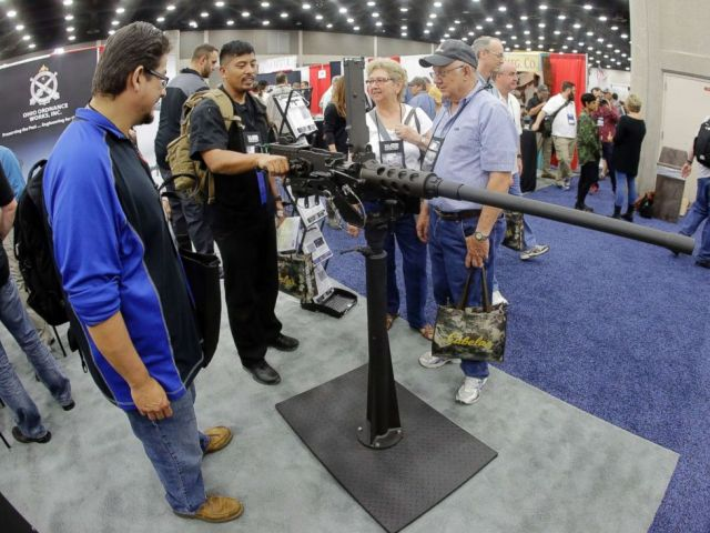 PHOTO: Retired Army Maj. Noel Zarza, center, of Bloomington, Ill., examines a .50 caliber machine gun at the National Rifle Association convention Saturday, May 21, 2016, in Louisville, Ky.