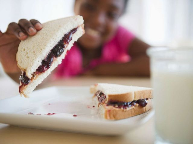 PHOTO: A girl picks up a peanut butter and jelly sandwich in an undated stock photo.