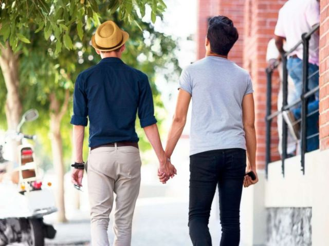 PHOTO: Two men hold hands while walking down a sidewalk in an undated stock photo.
