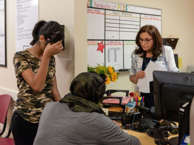 PHOTO: Aileen Dehnel, a case manager at the El Cajon Family Health Center, helps a Syrian mother and daughter check in.