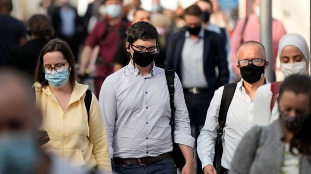 People wear face masks to curb the spread of coronavirus during the morning rush hour at Waterloo train station in London, Wednesday, July 14, 2021. Britain is bracing for acrimony on Monday, July 19 when the government lifts a legal requirement to w