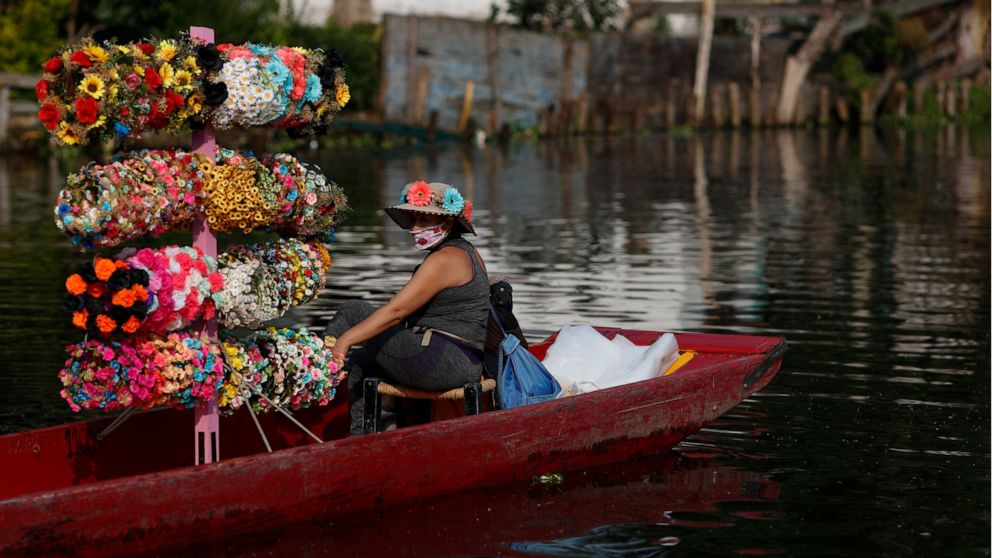 A flower crown vendor waits in her boat for revelers passing in colorfully painted wooden boats known as trajineras at the Nuevo Nativitas dock, as it opens once again to tourists and revelers amidst the ongoing new coronavirus pandemic, the Xochimil