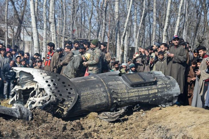 Indian soldiers and Kashmiri onlookers stand near the remains of an Indian Air Force helicopter after it crashed in Budgam district, on the outskirts of Srinagar on Feb. 27, 2019.