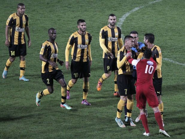 PHOTO: A player from Bnei Sakhnin, the only Arab team in the Israeli Premier league, scuffles with a player from Beitar Jerusalem at the Doha Stadium in the northern Arab-Israeli town of Sakhnin on Nov. 23, 2014.