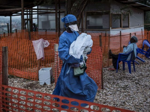 PHOTO: A caretaker already cured of Ebola is seen carrying a four day old baby suspected of having Ebola into a Medecins Sans Frontieres supported Ebola treatment center in Butembo, Congo, Nov. 4, 2018.