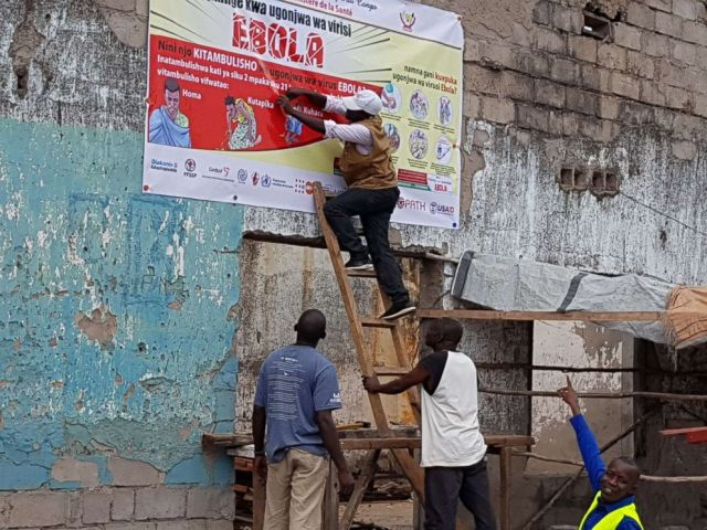 FOTO: Arbeiter fixieren in Tchomia, Demokratische Republik Kongo, ein Ebola-Poster zur Bewusstseinsbildung, um das Bewusstsein für Ebola in der örtlichen Gemeinde am 9. Oktober 2018 zu erhöhen.