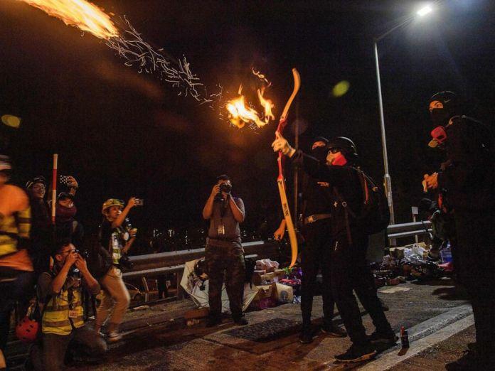 Manifestantes hacen uso de arcos y flechas con fuego | Anthony Wallace/AFP/Getty Images