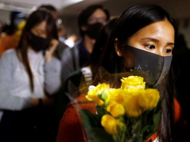 PHOTO:A woman pays tribute with flowers to Chow Tsz-lok in Hong Kong, China, Nov. 8, 2019.