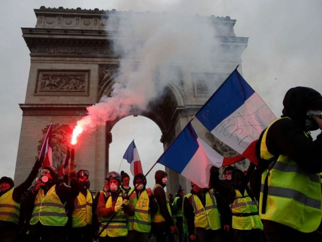 PHOTO: Protesters wearing yellow vests wave flares and French flags near the Arc de Triomphe during a demonstration over high fuel prices on the Champs Elysee in Paris, Dec. 1, 2018.