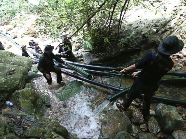 PHOTO: Thai soldiers drag water pipes that will help bypass water from entering a cave where 12 boys and their soccer coach have been trapped since June 23, in Mae Sai, Chiang Rai province, in northern Thailand, July 7, 2018.