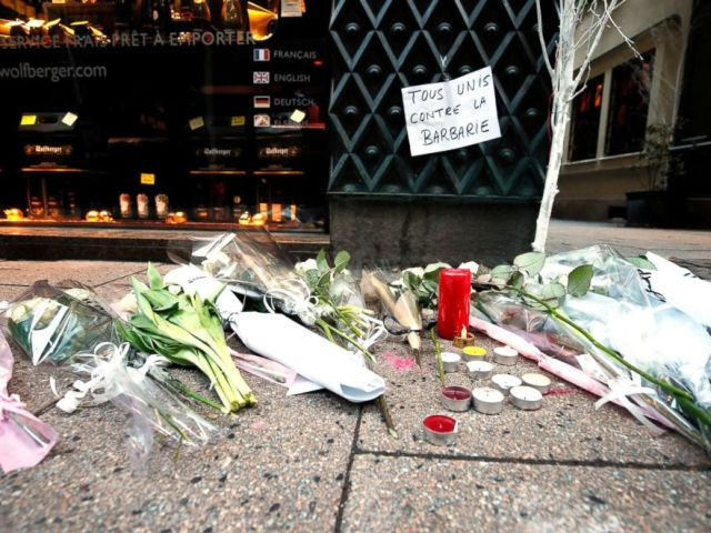 PHOTO: Candles, flowers and a sign reading All united against barbarity are left where a person was killed during the Christmas Market shooting in Strasbourg, France, Dec. 12, 2018.