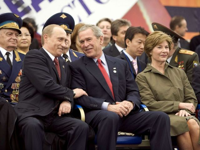 PHOTO: Former President George W. Bush, center, and Russian President Vladimir Putin, left, share a light moment as they sit with Laura Bush, right, and other heads of state during a military parade in Red Square in Moscow, May 9, 2005.