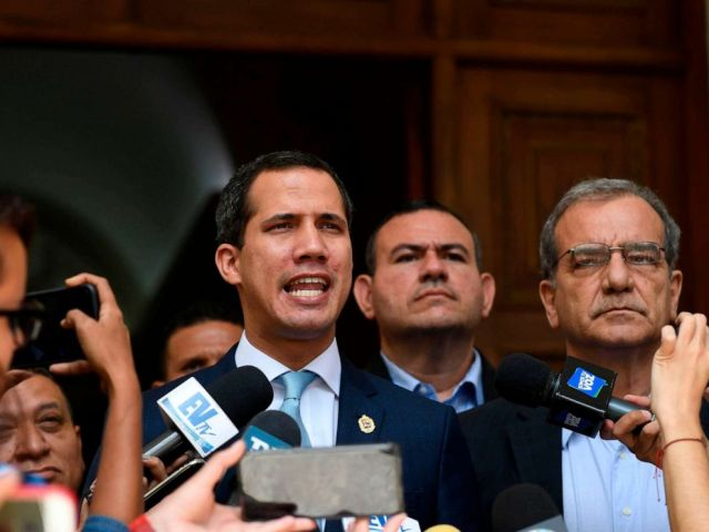 PHOTO: Venezuelan opposition leader and self-proclaimed acting president Juan Guaido (L) speaks to the press before a session at the National Assembly in Caracas on August 6, 2019.