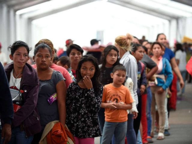 PHOTO: Central American migrants taking part in a caravan heading to the US, line up to borrow a sleeping pad, after arriving at a temporary shelter, set up in a stadium in Mexico City, Nov. 5, 2018.