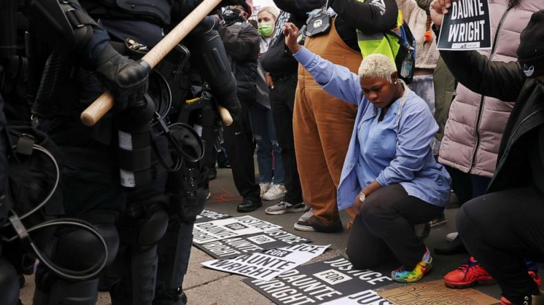 PHOTO: Evelyn Jarbah kneels as protesters take a moment of silence during a rally outside Brooklyn Center Police Department, a day after Daunte Wright was shot and killed by a police officer, in Brooklyn Center, Minn., April 12, 2021.