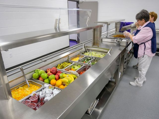 PHOTO: Michelle Hughes, head cook at Harrisburg High School, readies the serving line for lunch at the school on Feb. 14, 2019, in Harrisburg, Ill.