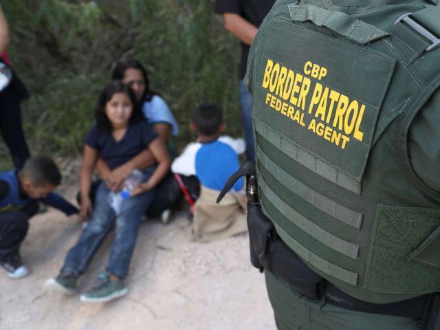 PHOTO: Central American asylum seekers wait as U.S. Border Patrol agents take them into custody on June 12, 2018 near McAllen, Texas.