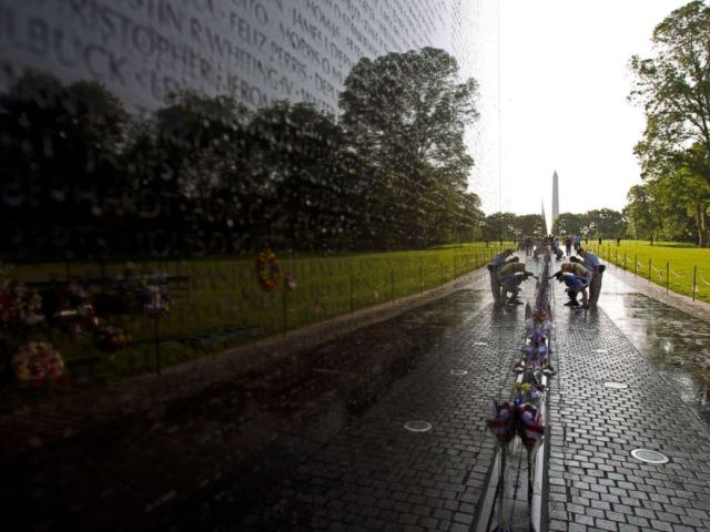 PHOTO: Visitor looks the names on the wall of the Vietnam Veterans Memorial in Washington DC, May 28, 2017.