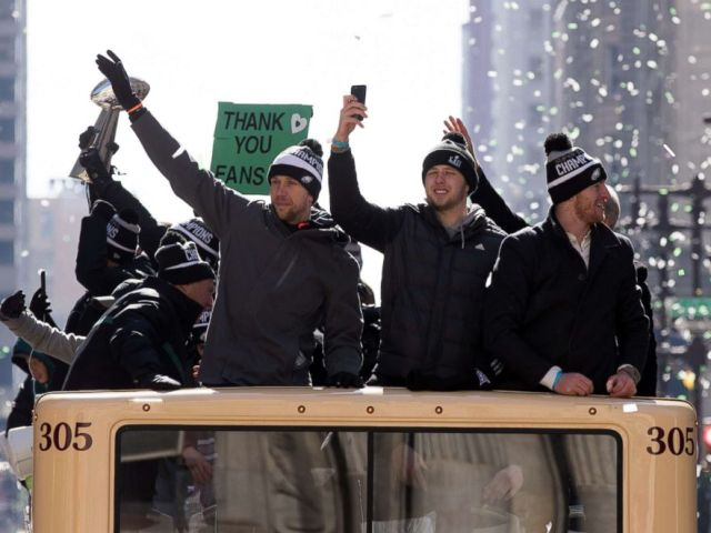 PHOTO: Philadelphia Eagles quarterbacks Nick Foles, Nate Sudfeld, and Carson Wentz ride atop a bus on the Super Bowl LII parade route in Philadelphia.