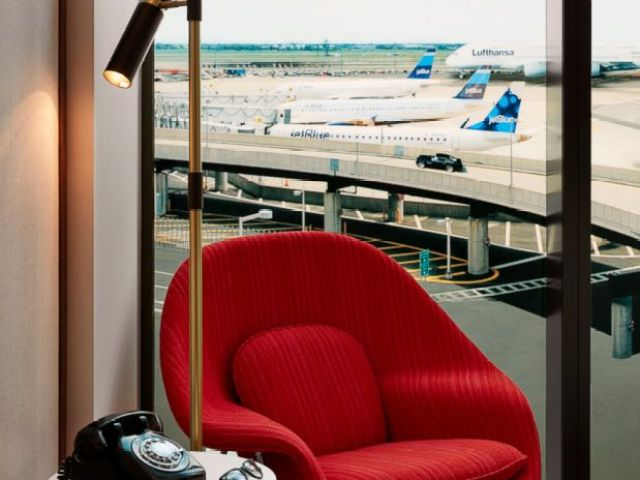 An authentic Eero Saarinen-designed Womb Chair sits beside a round white Saarinen Pedestal tulip side table where guests can make unlimited free international and local calls on a 1950s Western Electric 500 phone retrofitted converter by Old Phone Works.