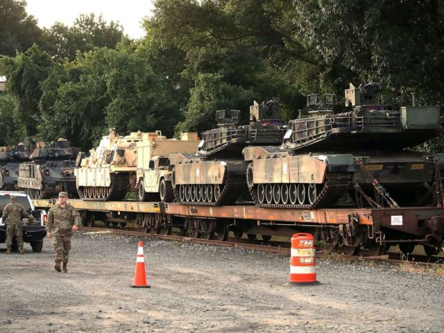PHOTO: Two M1A1 Abrams tanks and other military vehicles sit on guarded rail cars at a rail yard on July 2, 2019, in Washington, D.C.