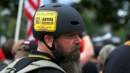"PHOTO: A man wears a sticker that says ""Antifa Hunting Permit"" at a Proud Boys rally in Portland, Ore., Aug. 17, 2019."