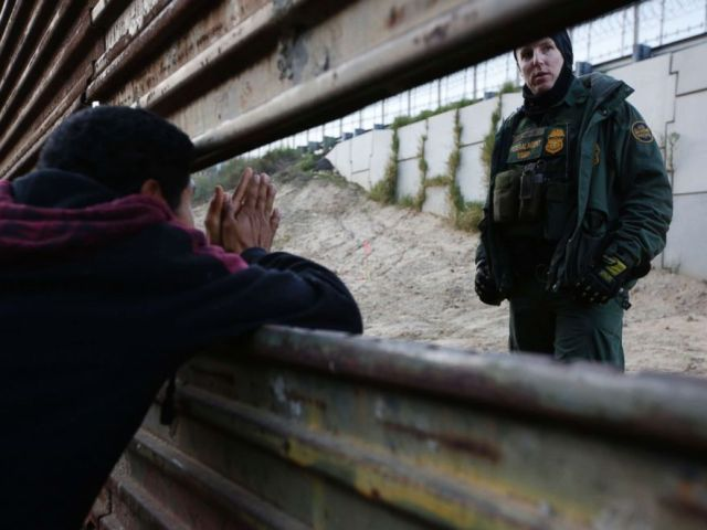 PHOTO: A Honduran migrant, left, talks with a Border Patrol agent as he tries to cross over the U.S. border wall to San Diego, California, from Playas in in Tijuana, Mexico, Dec. 15, 2018.