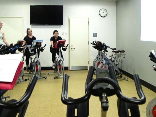 PHOTO: Fordham University professor Julita Haber teaches a business course while students are on spin bikes.
