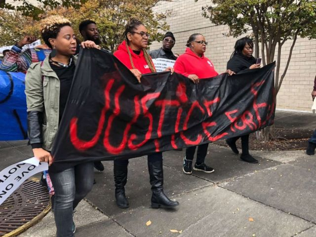 PHOTO: Protestors carry a sign reading Justice for E.J. during a protest at the Riverchase Galleria in Hoover, Ala., Nov. 24, 2018.