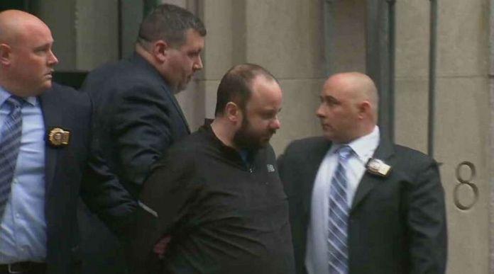 Marc Lamparello es llevado a la salida de Midtown North Precinct en Manhattan, Nueva York, el viernes 18 de abril de 2019, después de su arresto por supuestamente llevar latas de gas y líquido de encendedores a la catedral de San Patricio.