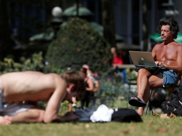 PHOTO: A man works on a computer in the sun at Bryant Park in New York, October 2, 2019.