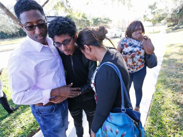 PHOTO: Family members embrace after a student walked out from Marjory Stoneman Douglas High School, Feb. 14, 2018, in Parkland, Fla.